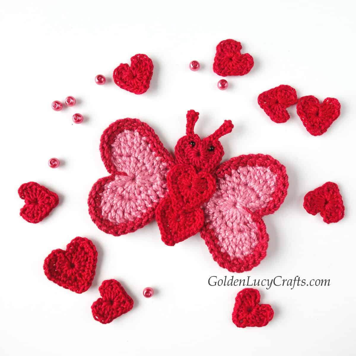 Crochet butterfly applique made from hearts, small hearts and beads around it.