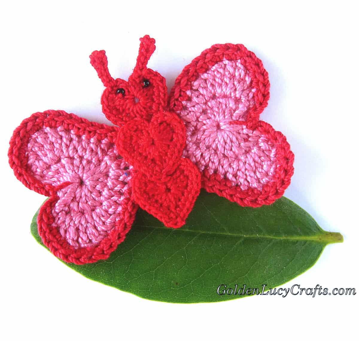 Crochet butterfly applique on the green leaf.