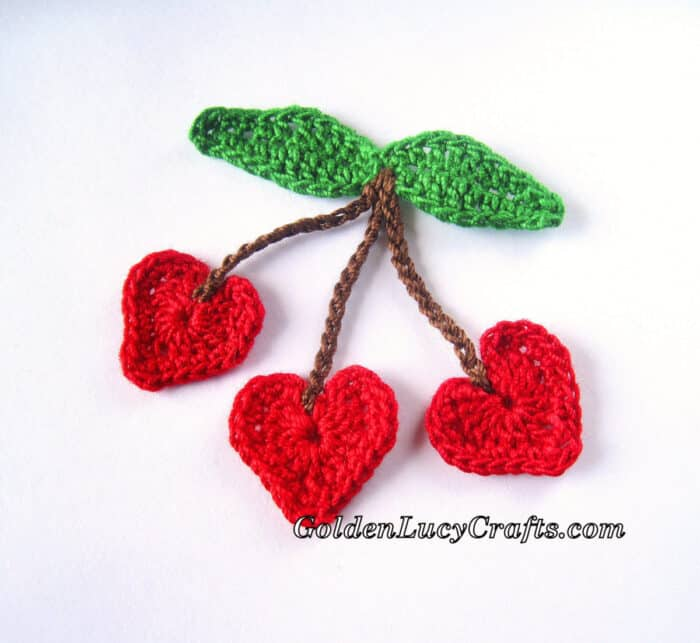 Crocheted three red heart-shaped cherries.