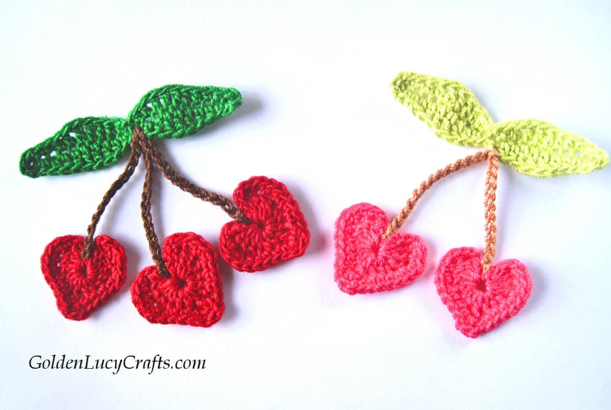 Tree red and two pink crocheted heart-shaped cherries.