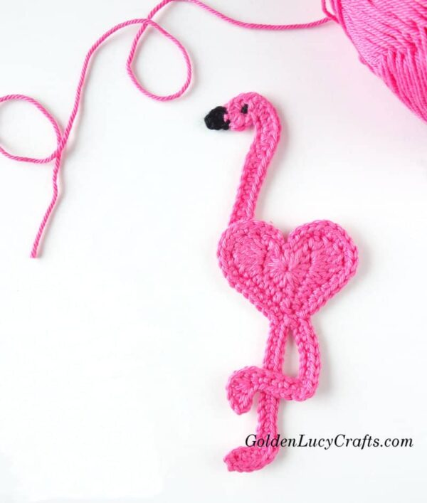 Crocheted heart-shaped flamingo, skein of yarn in the background.