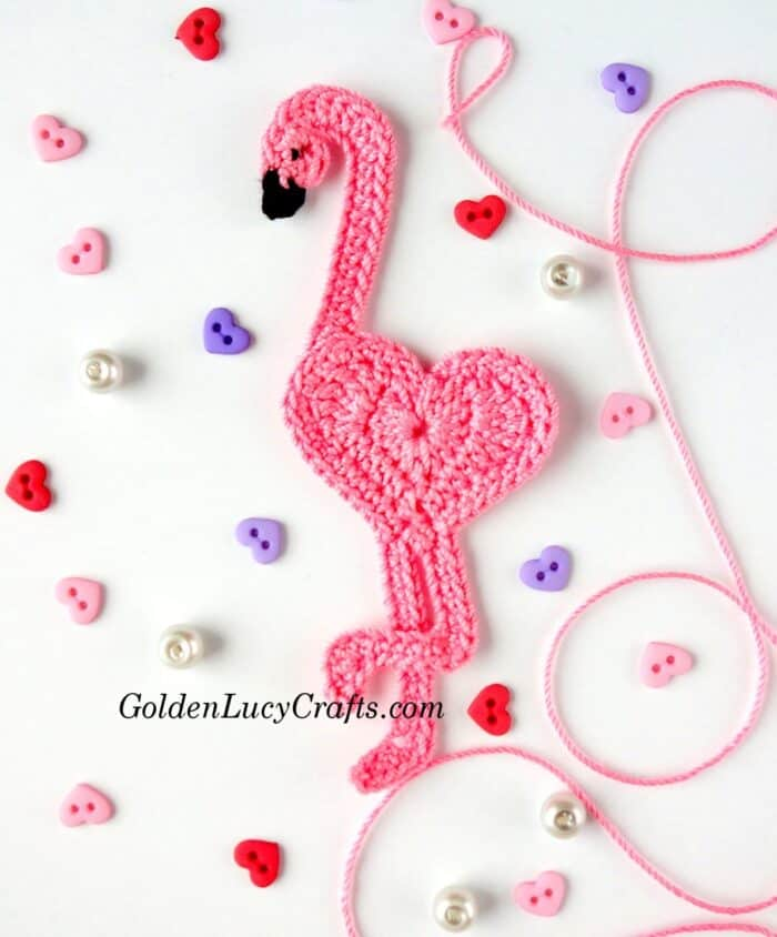 Crocheted pink heart-shaped flamingo applique, tiny heart buttons and pink thread.
