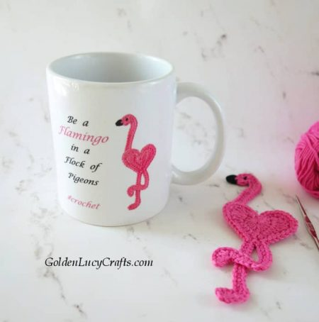 Mug with crocheted flamingo on it, crocheted pink flamingo laying next to it.