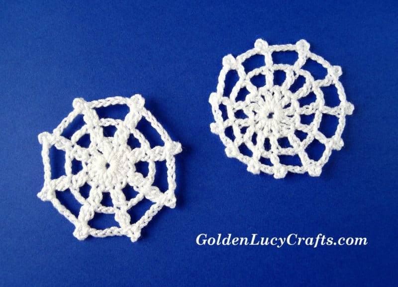 Two crocheted spider web appliques.