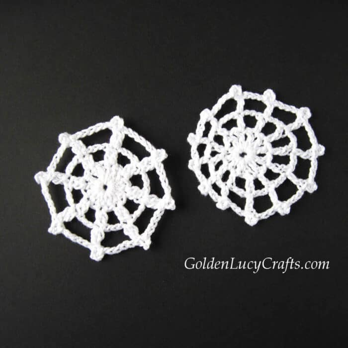 Two white crochet spider web appliques on black background..