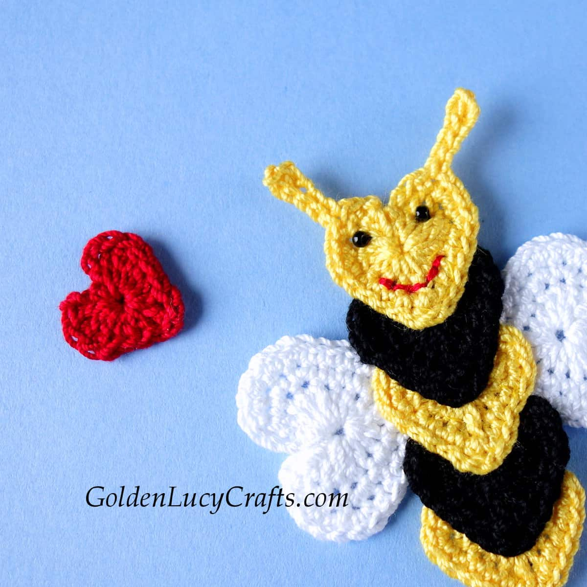 Crochet bee and small red heart, close up image.