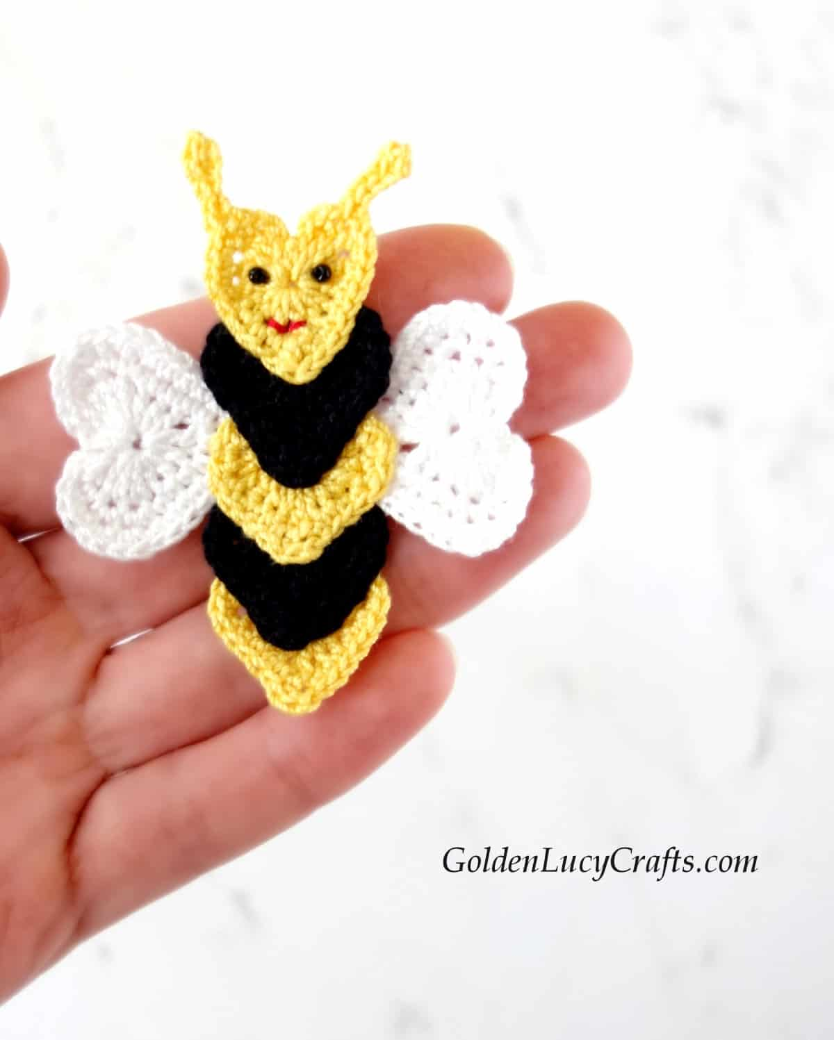 Crochet bee applique in the palm of a hand.