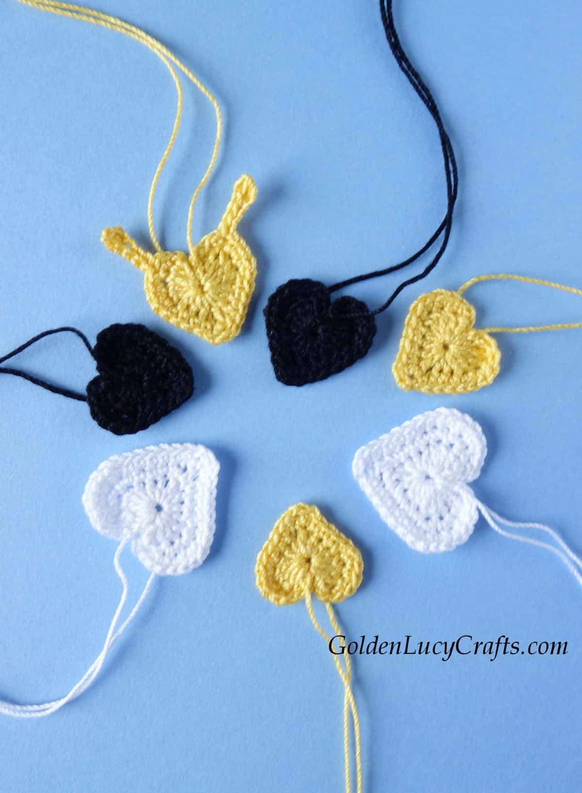 Pieces to make bee applique - crochet hearts in white, yellow and black colors.