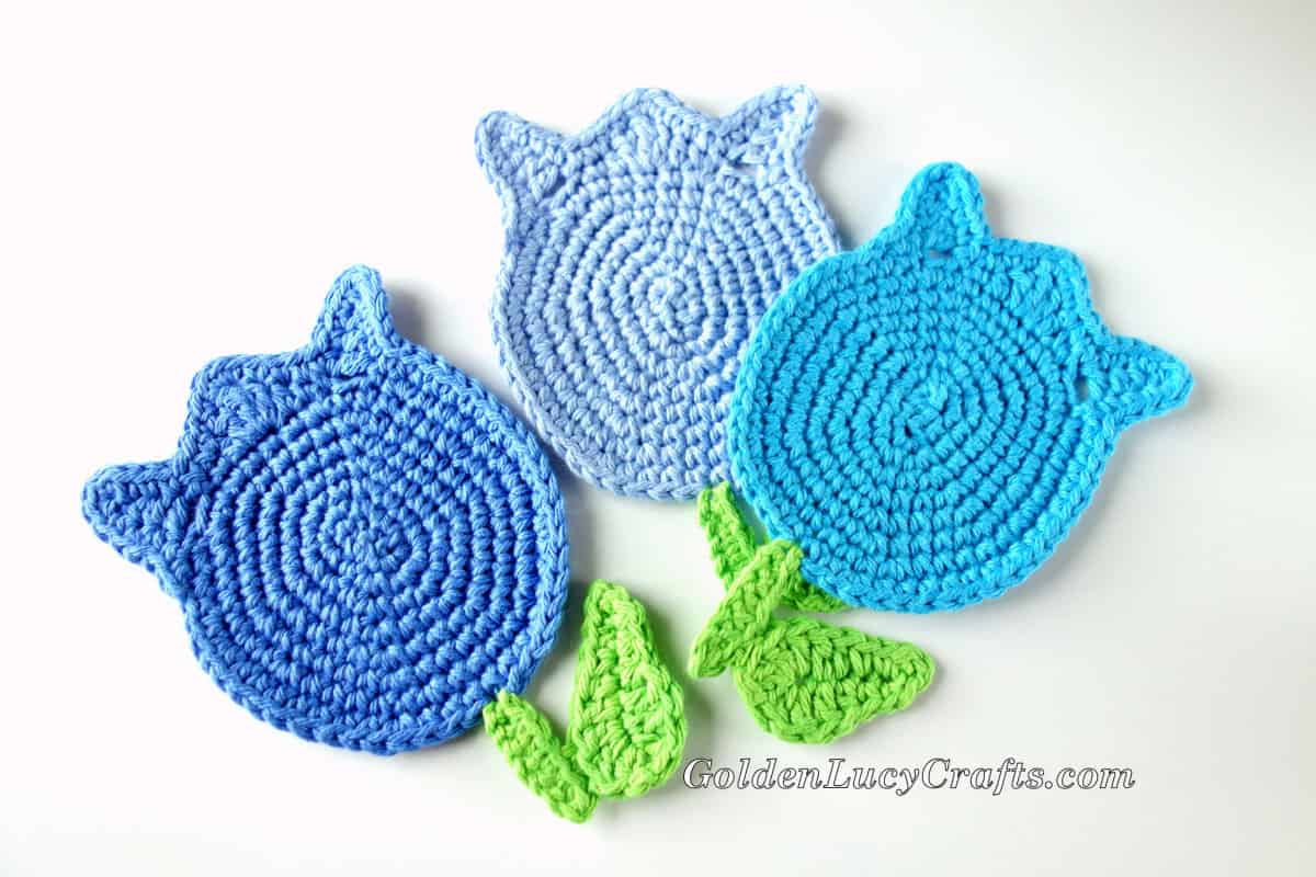 Three crocheted tulips in shades of blue.