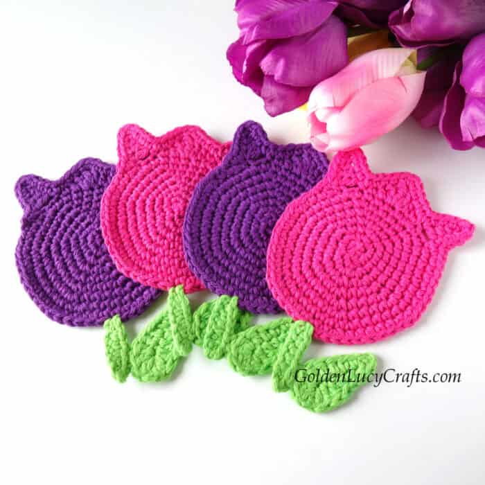 Crocheted tulip coasters in pink and purple colors.
