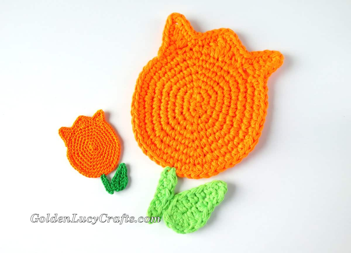 Large and small crocheted orange tulips.