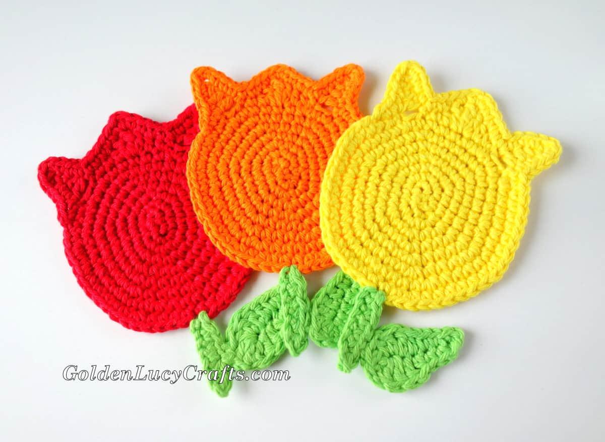 Three crocheted tulips - red, orange and yellow.