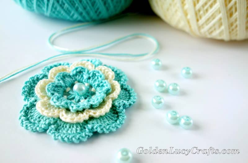 Crocheted flower Irish Rose in cream and aqua colors, beads and balls of thread in the background.