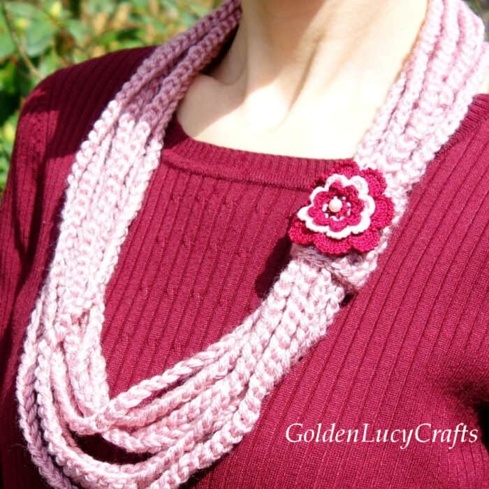 Crocheted pink scarf embellished with crocheted dark red rose.