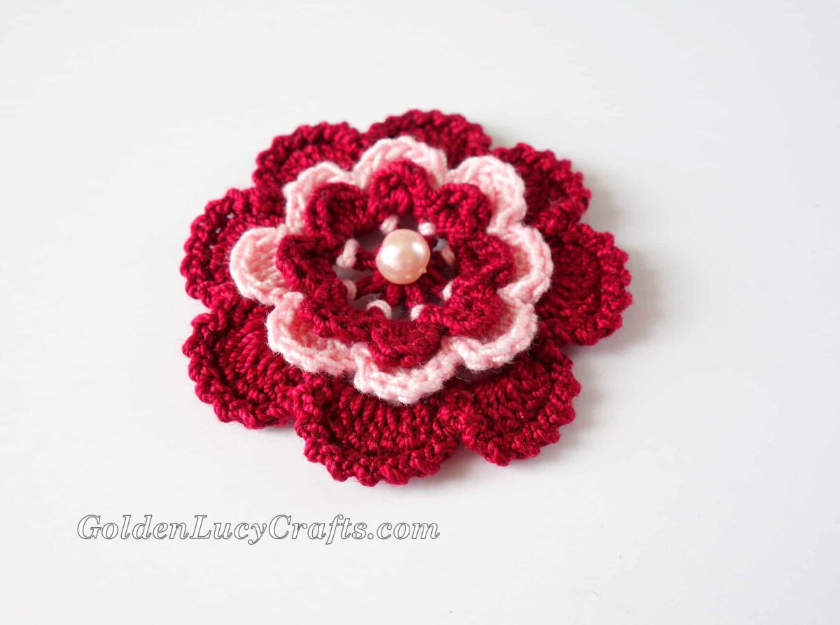 Crochet Irish rose in dark red and pink colors with bead in center.