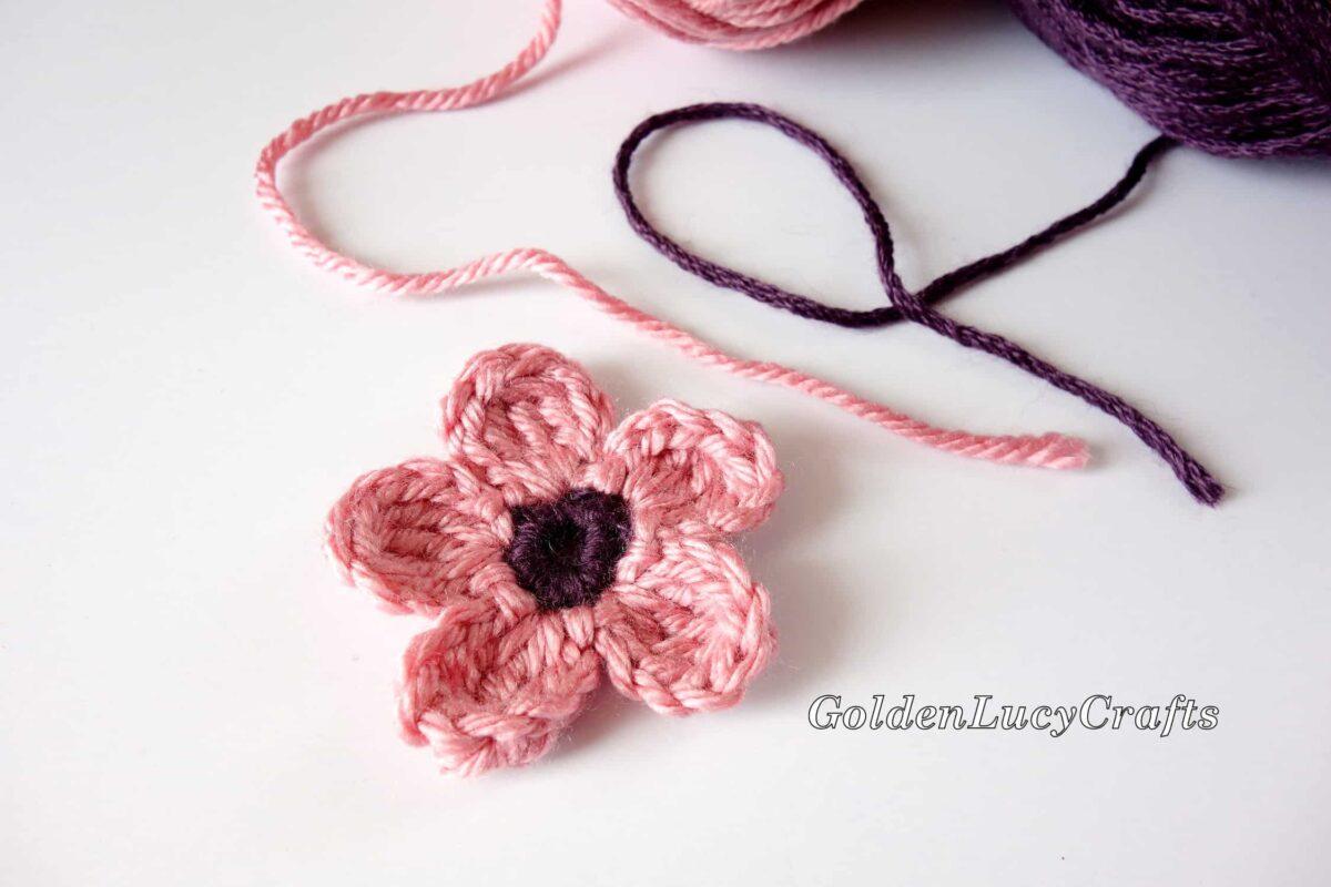 Crochet pink flower with dark purple center.