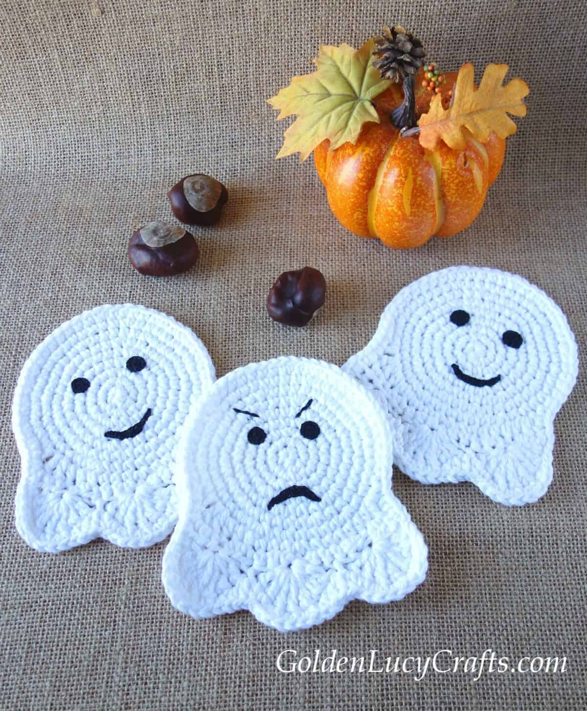 Three crocheted ghost coasters, pumpkin and three chestnuts.