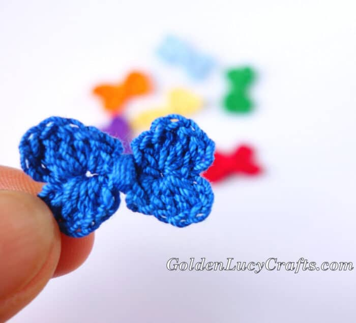 Crochet small bow held by fingertips.