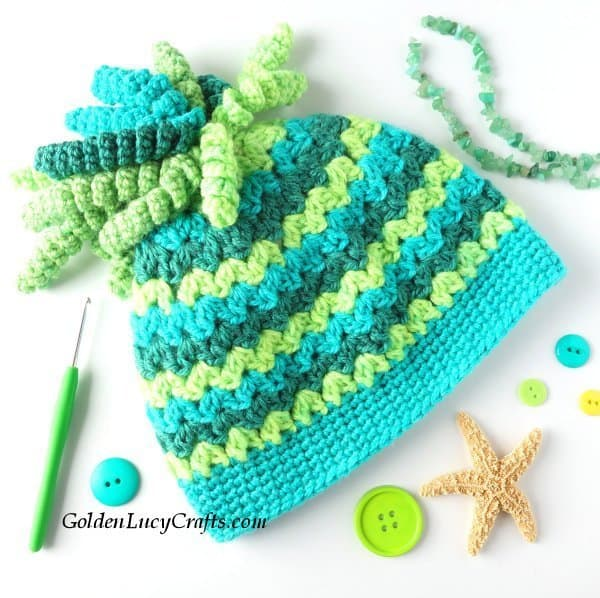 Crocheted hat in green, lemon and teal colors.