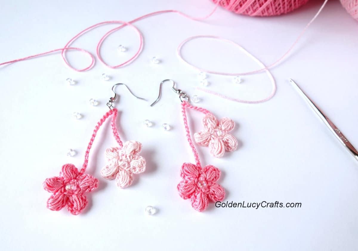 Crocheted cherry blossom earrings, beads, crochet hook and crochet thread in the background.