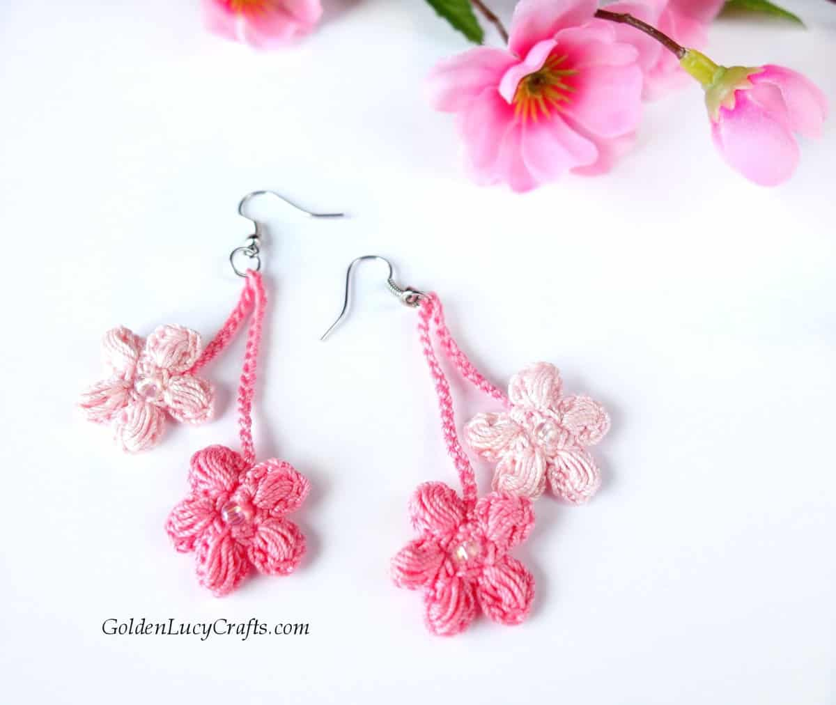 Crocheted cherry blossom earrings, cherry flowers in the background.