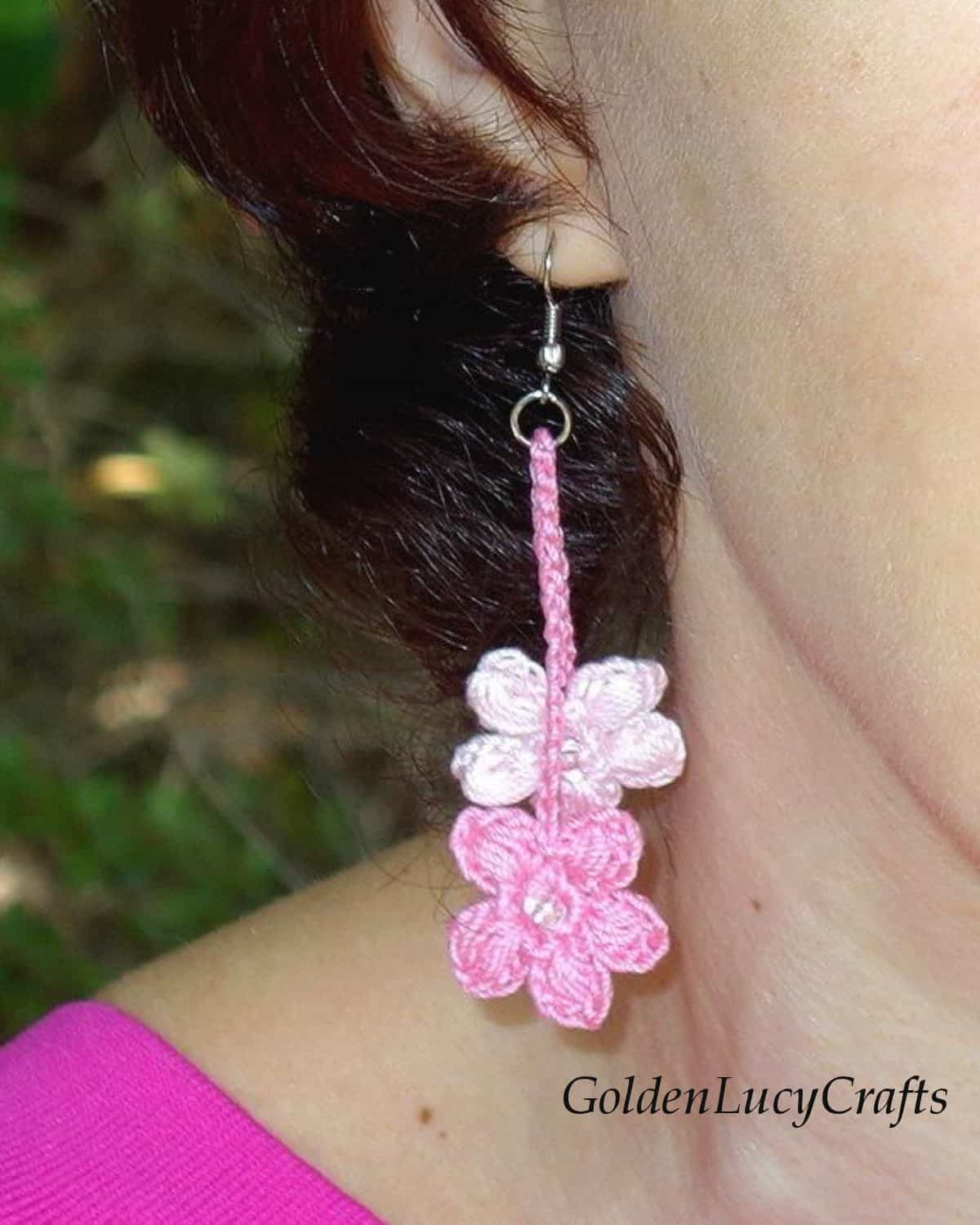 Model is wearing crocheted earring, close up image.