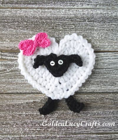 Crochet sheep applique with pink bow.