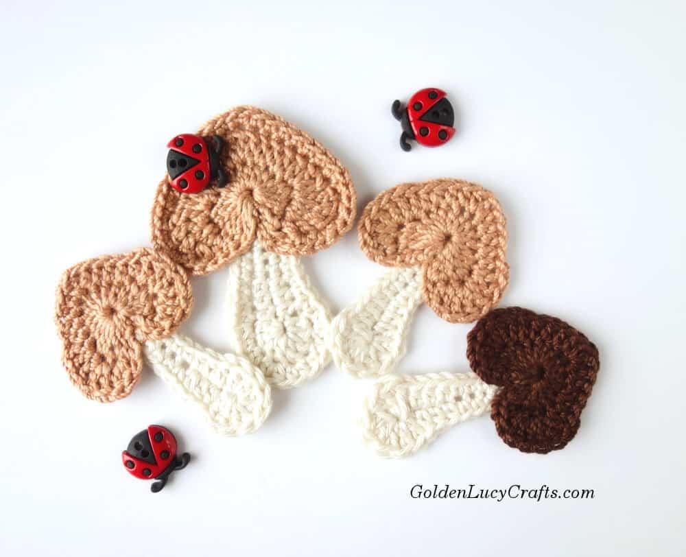 Four crocheted mushroom appliques.
