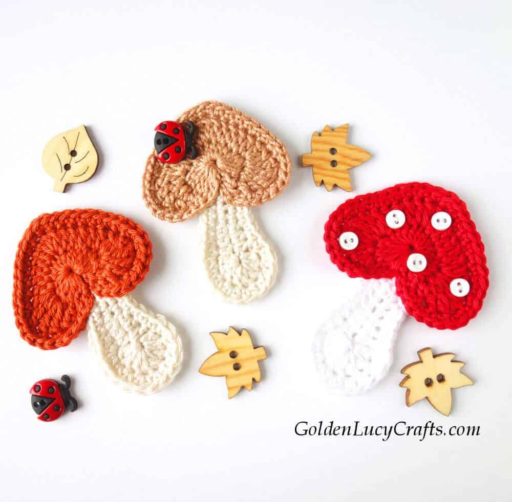 Three crocheted mushroom appliques, craft buttons.