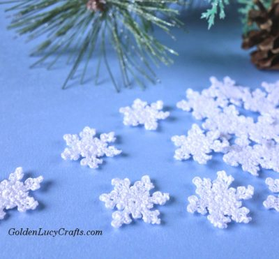 Small crocheted snowflakes, Christmas tree branch in the background.