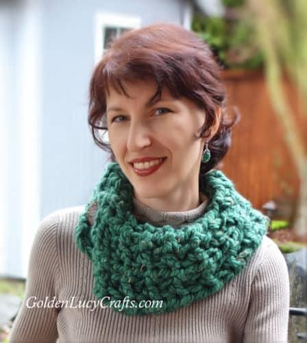 Model wearing crocheted green cowl.