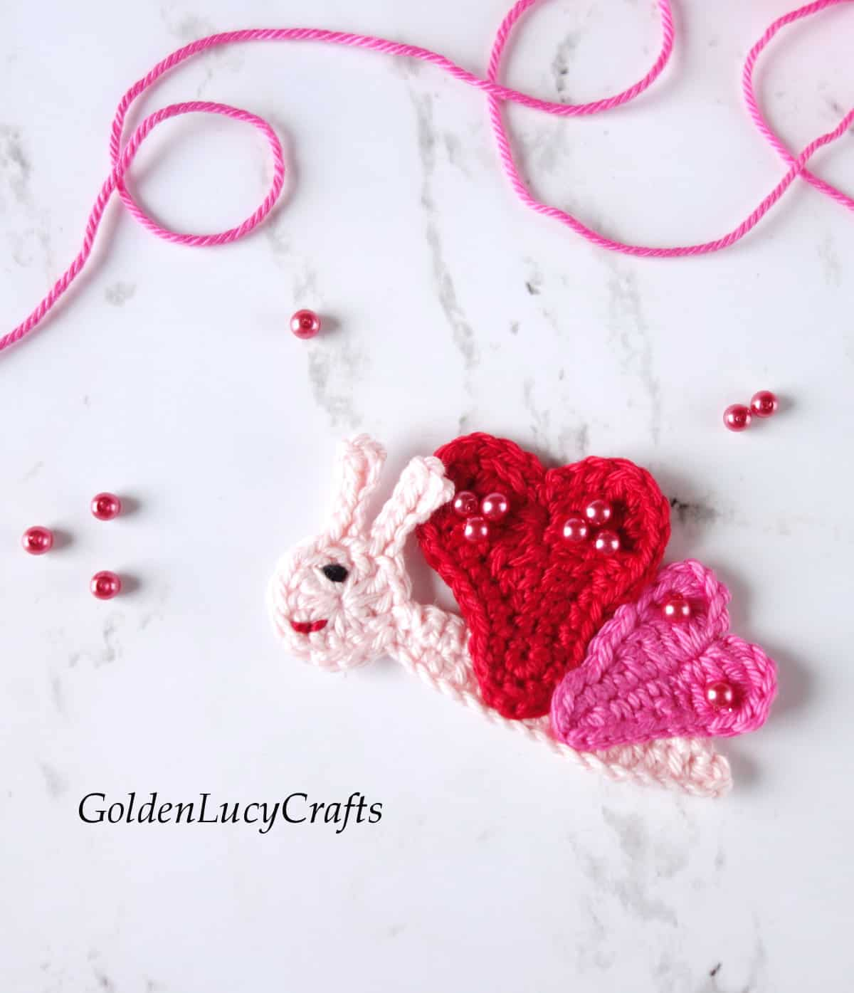Crochet butterfly applique in pink and red color with heart-shaped wings.