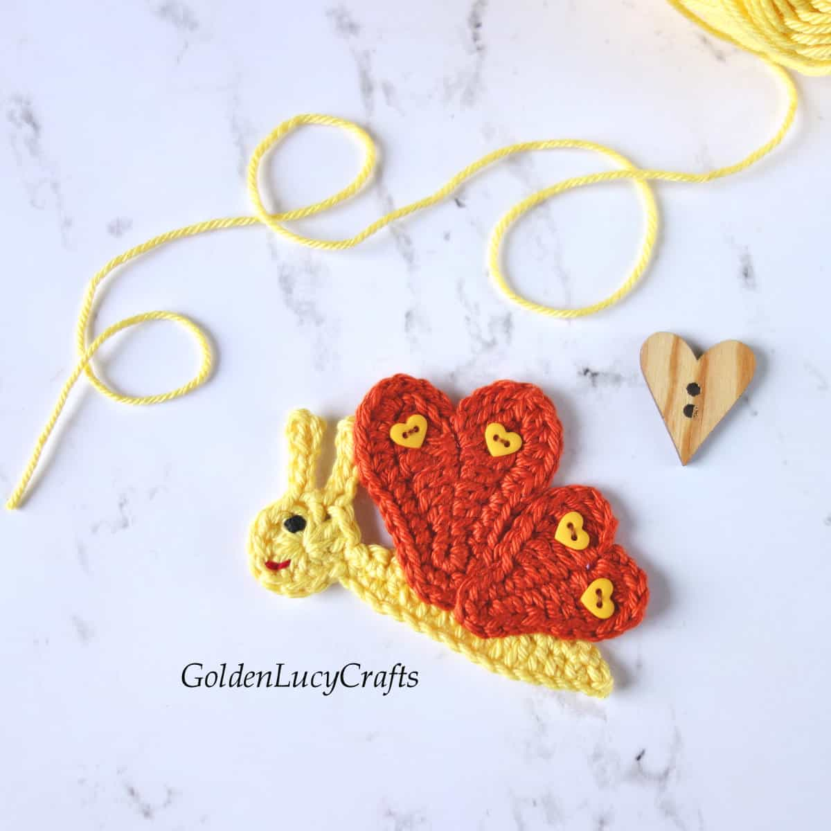 Crochet butterfly applique in yellow and brown color with heart-shaped wings.