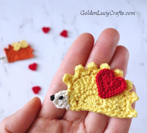 Crochet hedgehog applique in the palm of a hand.