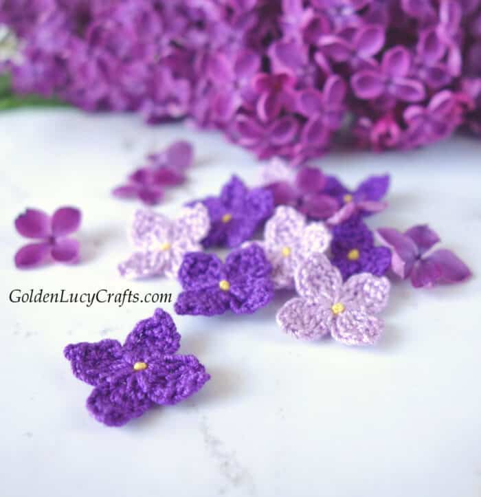 Crocheted lilac flowers, real lilac in the background.