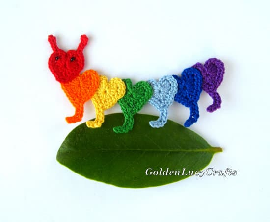 Oruga de ganchillo hecha de corazones en colores arcoiris.