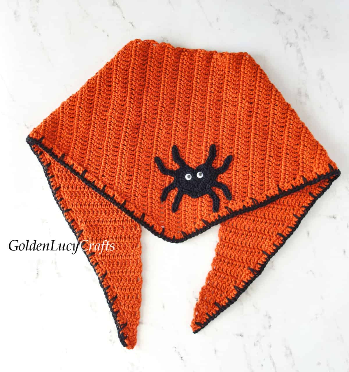 Crochet orange bandana embellished with spider applique.