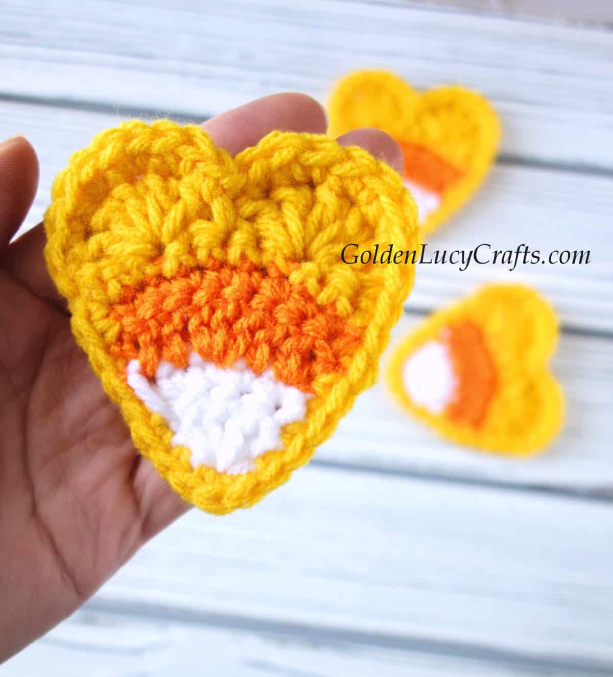 Crocheted candy corn heart in the palm of a hand.