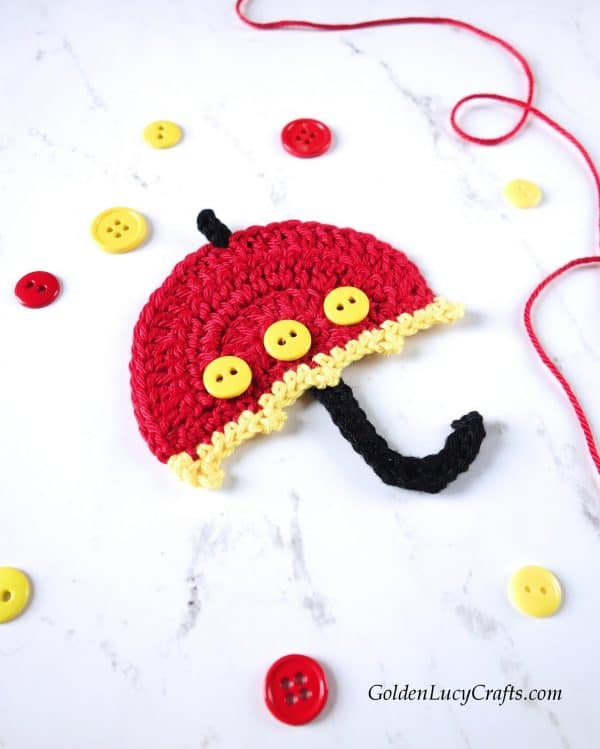 Crochet red umbrella applique embellished with yellow buttons