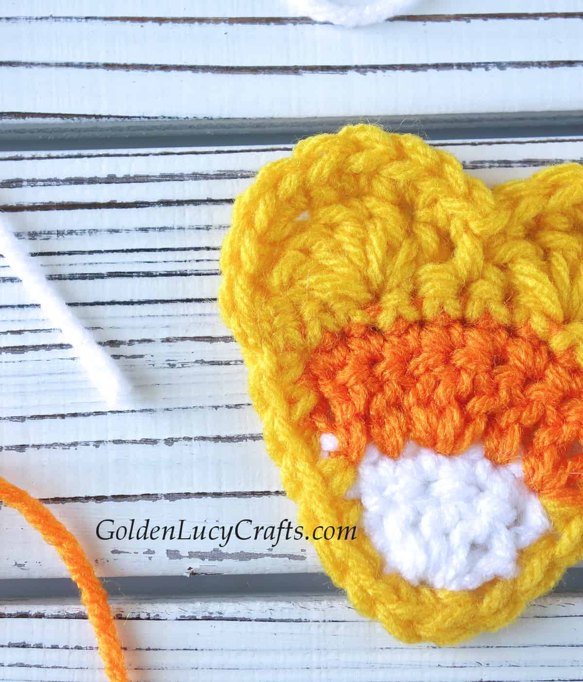 Crocheted candy corn heart close up image.