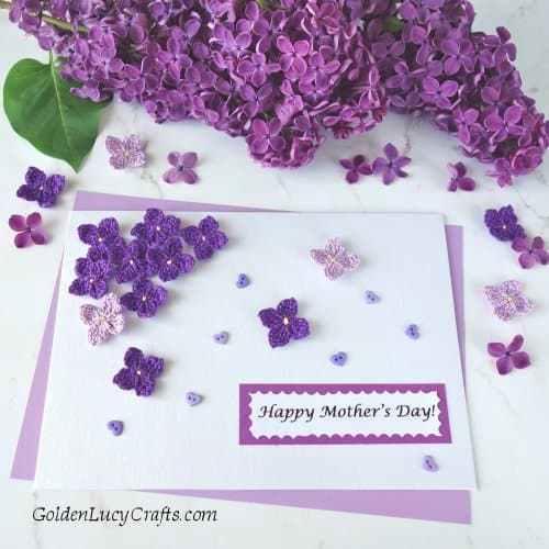 Handmade card embellished with crochet lilac flowers, lilac branch laying next to it