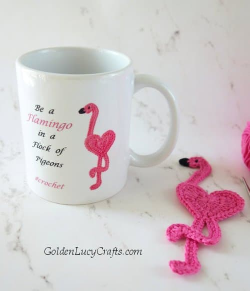 Mug with crochet flamingo on it and crochet flamingo applique laying next to it