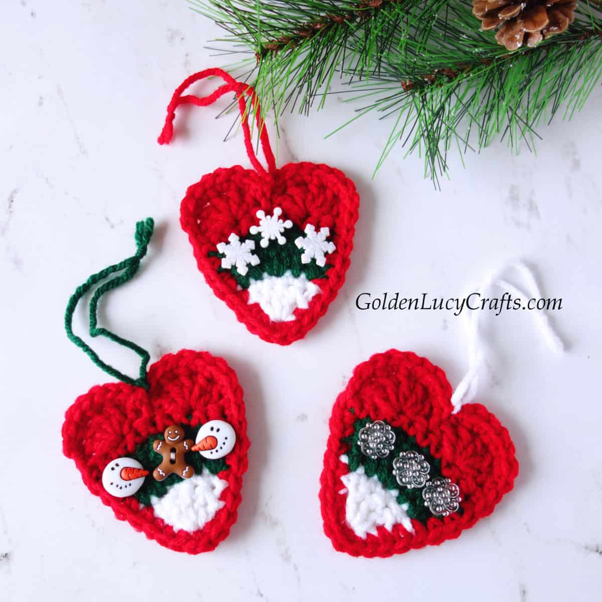 Crochet Christmas heart ornaments in red, white and green embellished with buttons.