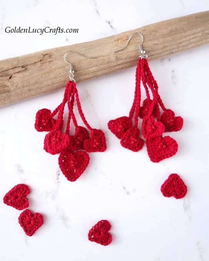 Crochet heart earrings laying on a piece of wood, small hearts laying around.