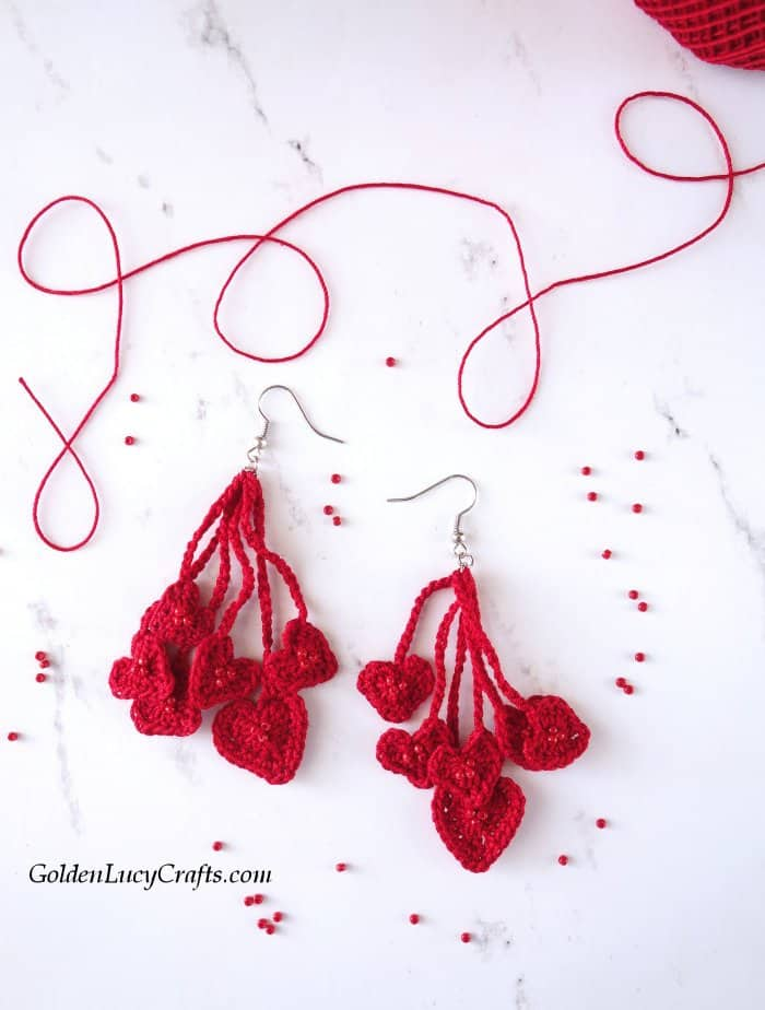 Crochet heart earrings, seed beads spilled around.