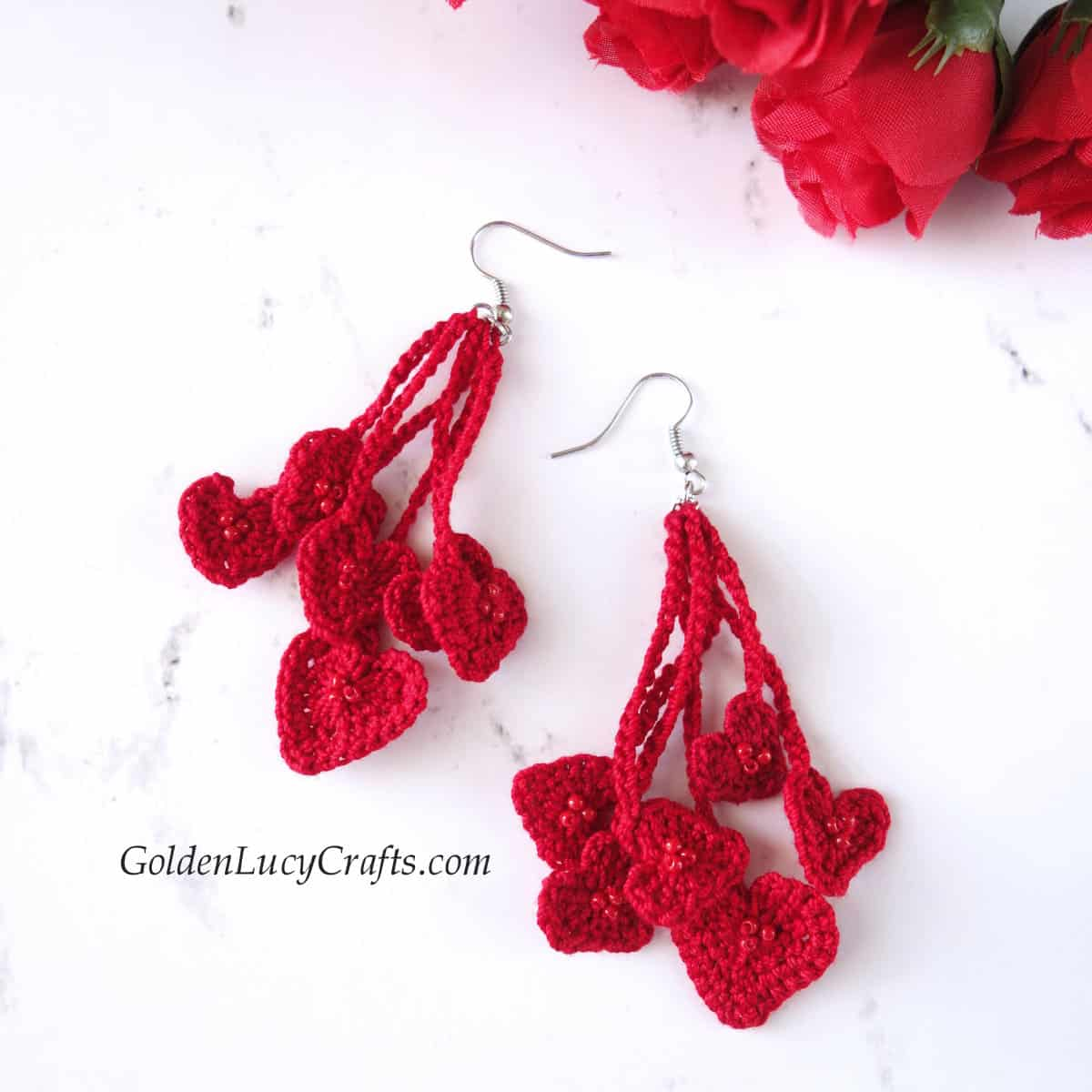 Crochet red heart earrings, roses on the background.