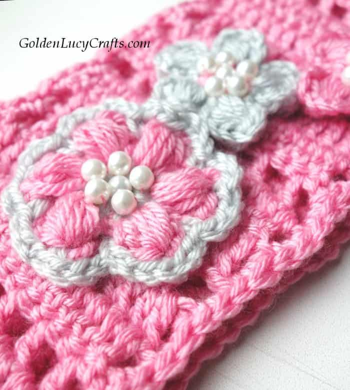 Crochet headband embellished with flowers and beads, close up picture.