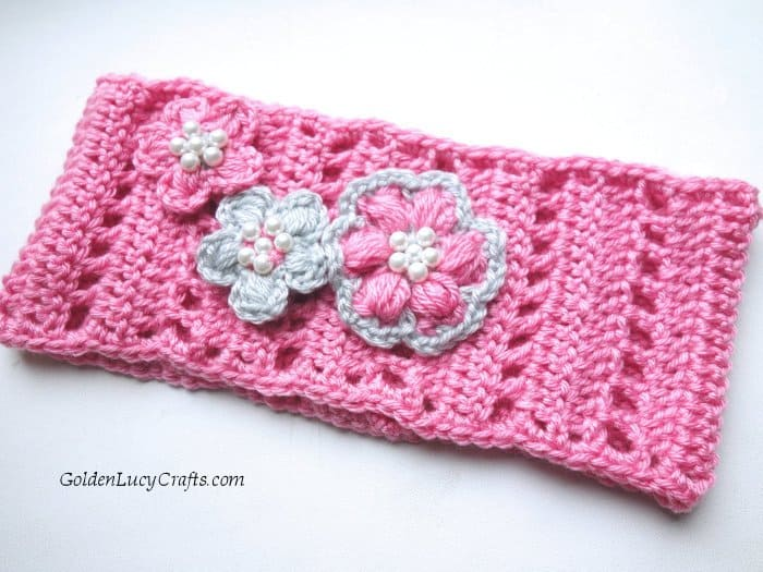 Crochet pink headband embellished with crocheted flowers and beads.