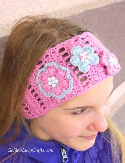 Young girl is wearing pink crochet headband embellished with flowers