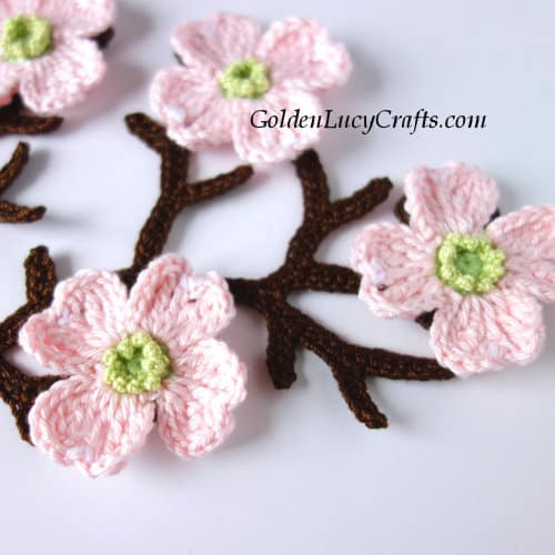 Crocheted dogwood tree branch with flowers.